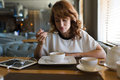 Nice woman breakfast in cafe after work on her digital tablet portrait of young charming female drinking tea and tastes yummy Royalty Free Stock Photo