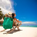 Nice woman relaxing in the wooden chair on white beach Stock Photos