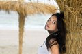 Nice young brunette on a beach near the palm tree Stock Photos