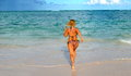 Nice young girl is running in the ocean Stock Photos