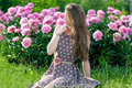 Nice young woman in the park near peonies Royalty Free Stock Photo