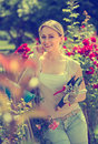 Nice young woman working with bush roses with horticultural tool Royalty Free Stock Photo