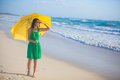 Nice young woman with yellow umbrella walking alone on the beach this image has attached release Stock Photography