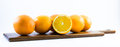 Nicely colored oranges on a white background - front and back lined next to each other on a wooden board Royalty Free Stock Photo