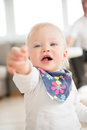 Nicely dressed and happy baby girl pointing with finger. Royalty Free Stock Photo