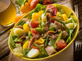 Nicoise salad over wood background Stock Photos
