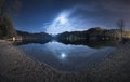 Night in alpsee lake in germany beautiful landscape with mountains forest stars full moon and clouds reflected water Royalty Free Stock Photography