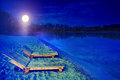Night beach landscape with two wooden sunbeds bank of lake in the in autumn Stock Image