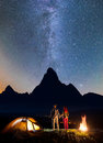 Night camping. Romantic hiker couple - girl and guy holding hands, standing near tent and campfire, enjoying starry sky Royalty Free Stock Photo