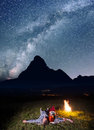 Night camping. Romantic lovers lying near the fire and enjoying incredibly beautiful starry sky. Long exposure Royalty Free Stock Photo