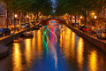 Night city view of amsterdam canal and luminous track from the b with bridges boat holland netherlands Stock Photos