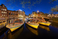 Night cityscape with traditional old houses and boats in Amsterdam Royalty Free Stock Photo