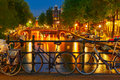 Night illumination of amsterdam canal and bridge with typical dutch houses boats bicycles holland netherlands Stock Photos
