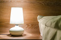 Night lamp on a nightstand illuminating the bed with wood texture in background Royalty Free Stock Photography