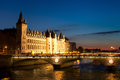 Night in paris the pont au change bridge over river seine and the conciergerie a former royal palace and prison france Stock Photography
