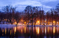Night scene in park. Trees reflecting in water at dawn
