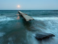 Night sea surf, ruined pier and Moon in sky (Black Sea, Bulgaria Royalty Free Stock Photo