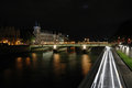 Night shot of the pont au change paris over seine river in france Stock Image