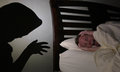 Night terror woman in bed screaming with as a shadowy intruder approaches or having a nightmare Royalty Free Stock Photo