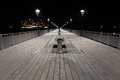 Night view of a  boardwalk, bench and lamp posts Royalty Free Stock Photo
