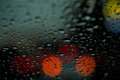 Night view of the city lights through the window in the rain, rain drops falling on the windshield of the car. Abstract Royalty Free Stock Photo