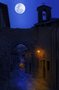 Night view of narrow street in small town between old houses under the sky with full moon tende france Stock Image