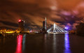 Night view at riga latvia panorama of skyscrapers and cable stayed bridge over the river of daugava with beautiful dark clouds Stock Photography