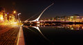 Night view of the samuel beckett bridge in dublin city centre ireland july by architect santiago calatrava reflecting river liffey Royalty Free Stock Photo