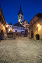 Night view of a small tower in sibiu romania street with the evangelical church the background photographed at the blue hour Stock Images