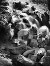 Night winter view to frozen cascade of waterfall icy twigs and icy boulders in foam of rapid stream reflections of light in Stock Image