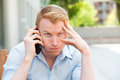 Nightmare phone calls closeup portrait young man annoyed frustrated pissed off by someone talking on his mobile bad news outdoors Royalty Free Stock Photography