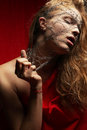 Nightmare of a young glamourous ginger girl in red cloth wire on face studio shot Royalty Free Stock Photography