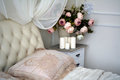 On the nightstand beside the bed is a vase with flowers and candles Royalty Free Stock Photo