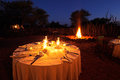 Nighttime campfire and table decorated for outdoor safari catering Royalty Free Stock Image