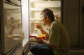 Nighttime sleep walking related eating disorder a man who has is as he sits in front of an open refrigerator ice cream Stock Photo