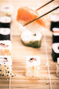 Nigiri sushi and chopsticks a salmon being picked up with with different types of maki pieces on a wooden mat in the Stock Image
