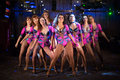 Nine beautiful showgirls in purple costumes posing on stage Royalty Free Stock Photography