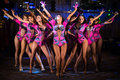 Nine showgirls in purple costumes with raised hands perform