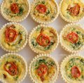 Nine small individual quiche each topped with a slice of tomato on a white plate Stock Photography