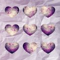Nine small violet hearts with triangle pattern hipster and lace like outline on textured background looks like crumpled paper Stock Images