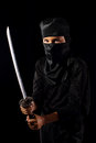 Ninja kid little boi playing with katana in costume on dark background Royalty Free Stock Image