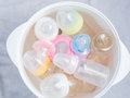 Nipple teethers and milk bottles in steam sterilizer and dryer used for sterilize baby accessories by high Stock Photos