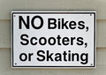 No bikes sign a black and white that reads scooters or skating Stock Photography