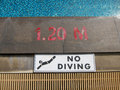 No diving sign and pool depth markings on swimming pool edge Stock Photo