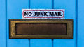 No junk mail a brass letter box with a sign above indicating new wanted Stock Image