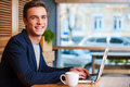 No minute without my laptop handsome young man working on and smiling while enjoying coffee in cafe Royalty Free Stock Photography