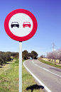 No overtaking sign in a secondary road bordered for olive trees and almond trees full bloom Stock Images