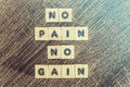 No pain no gain message written with wooden blocks on a wooden table Royalty Free Stock Image