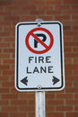 No parking fire lane sign front red brick wall Stock Images
