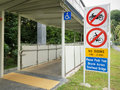 No riding on overhead bridge signs at the entrance to that shares the walkway with persons wheelchairs Royalty Free Stock Photo